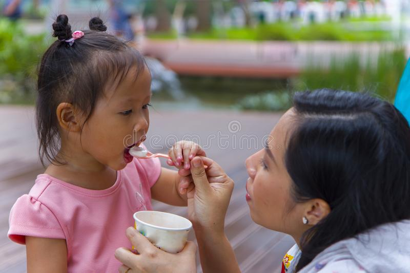 Mom with her 3 years old daughter walking along city street and eating ice cream. Good relations of parent and child. Happy. Moments together.  High resolution royalty free stock photography