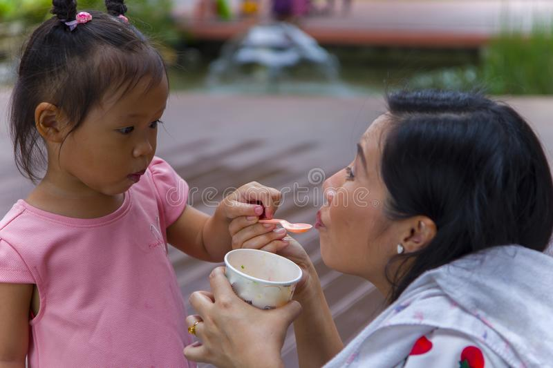 Mom with her 3 years old daughter walking along city street and eating ice cream. Good relations of parent and child. Happy. Moments together.  High resolution stock image