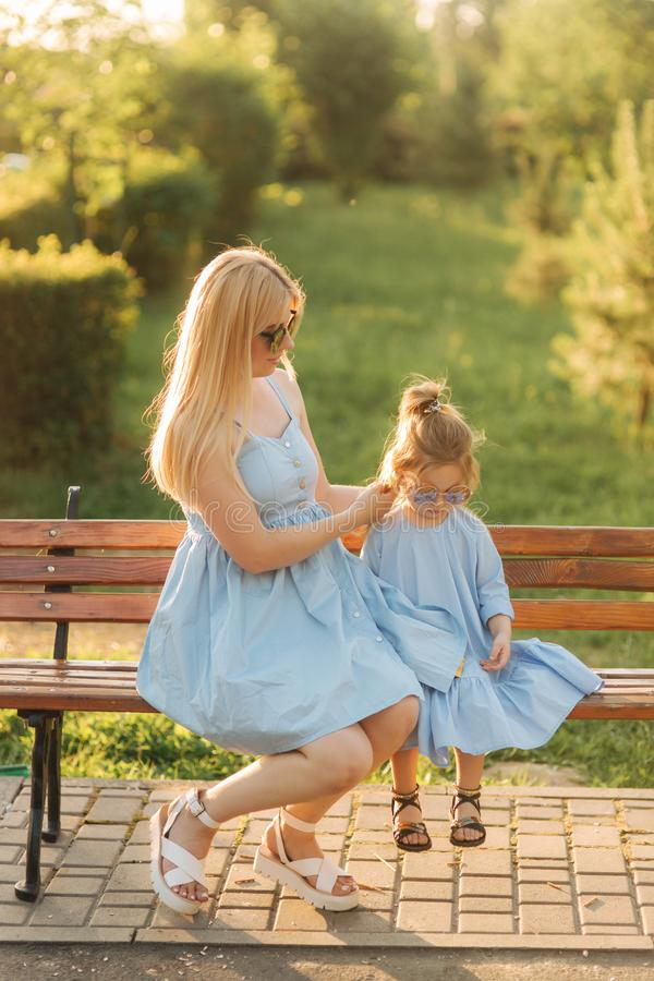 Mom and his little daughter are sitting on a bench in the park royalty free stock images