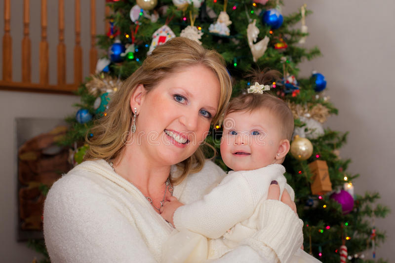 Download Mom Holding Cute Infant Baby In Front Of Christmas Tree Stock Photo - Image: 32728332