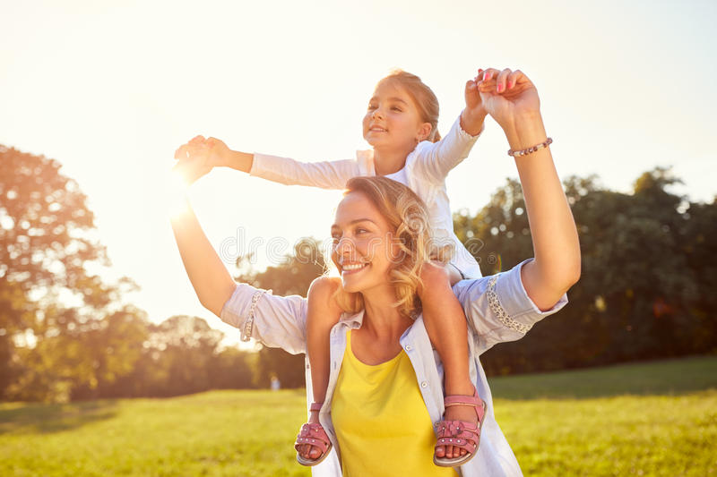 Mom holding daughter on shoulders stock image