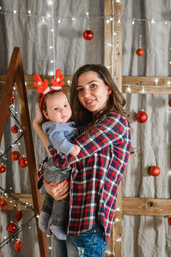 Mom holds in her arms a child with red horns. against the background of the new year. Theme Christmas holidays winter new year. A. Young stylish Caucasian stock photography
