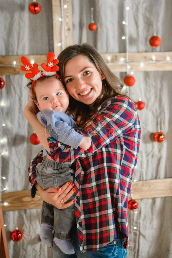 Mom holds in her arms a child with red horns. against the background of the new year. Theme Christmas holidays winter new year. A. Young stylish Caucasian stock photo