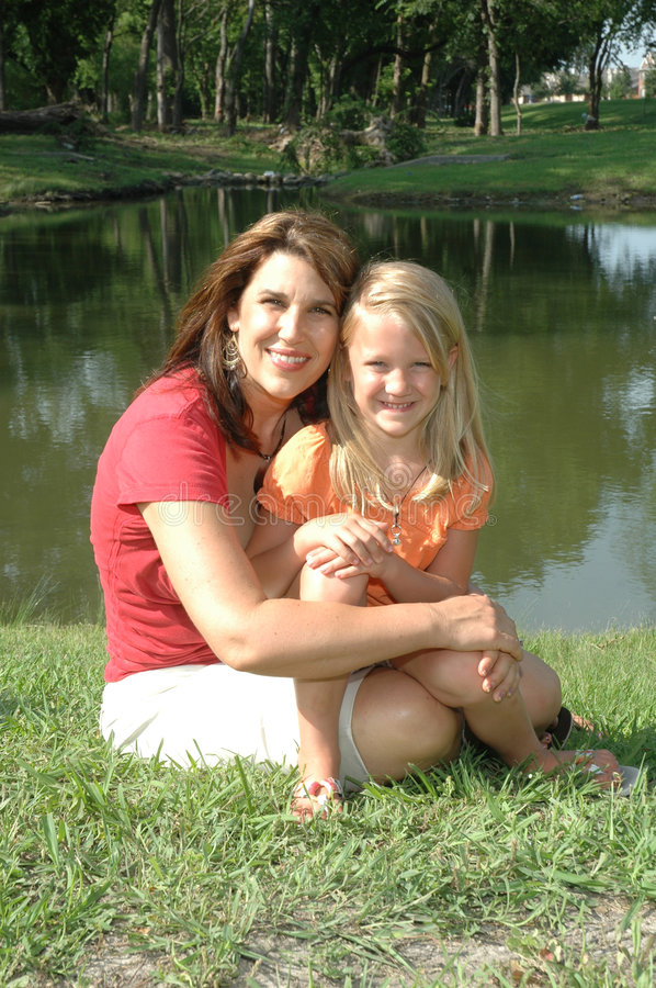 Mom hugging daughter outdoors royalty free stock images