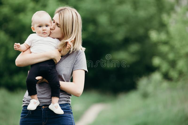 Mom hugging and kissing baby daughter royalty free stock image