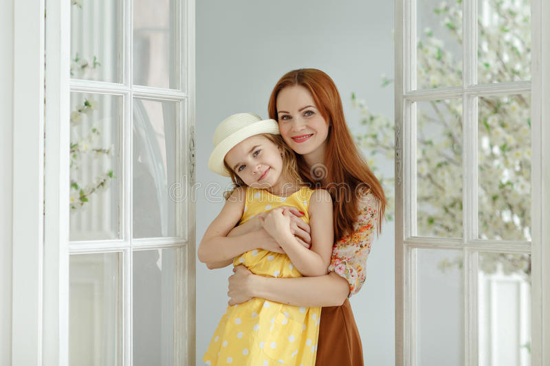 Mom hugs daughter`s blonde and smiles in bright studio, spring stock photos