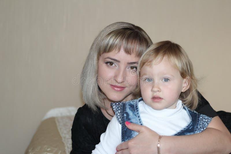 Mom hugs little blue-eyed daughter.  stock images