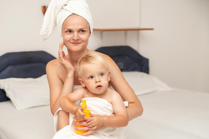 Mom and infant baby in white towels after bathing apply sunscreen or after sun lotion or cream. Children skin care in a hotel or. Bedroom. Spf, skin moisturizer stock photography