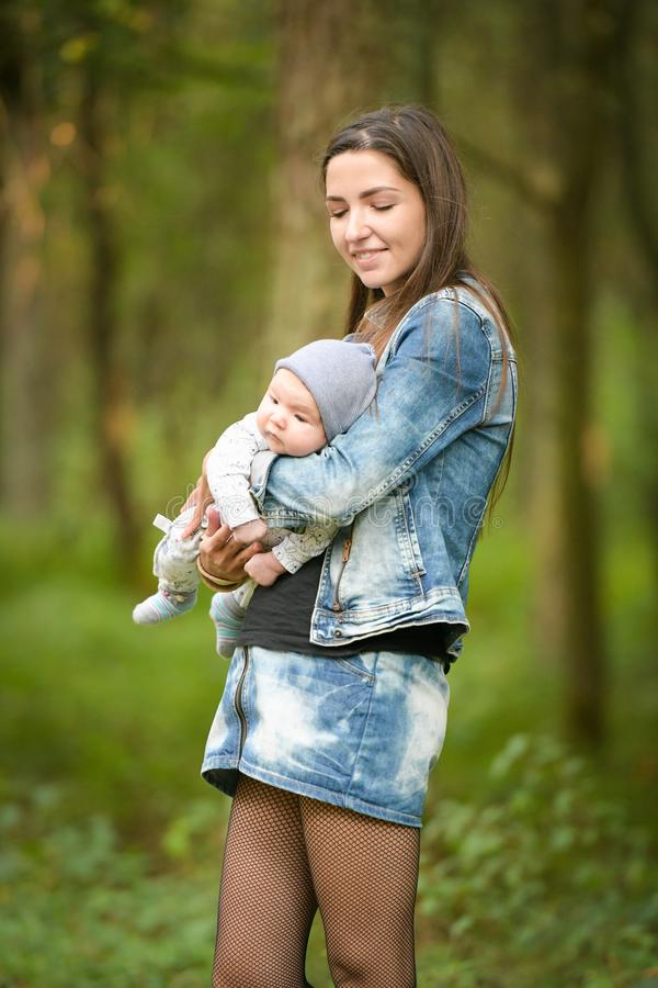Mom in jeans with a baby. mother and her little daughter park royalty free stock photos