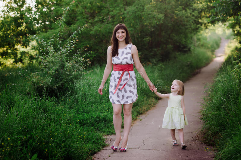 Mom keeps daughter's hand and walks the walk on the nature in sunset light. Motherhood, child, family stock photography