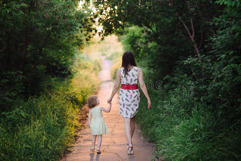 Mom keeps daughter's hand and walks the walk on the nature in sunset light. Motherhood, child, family stock images