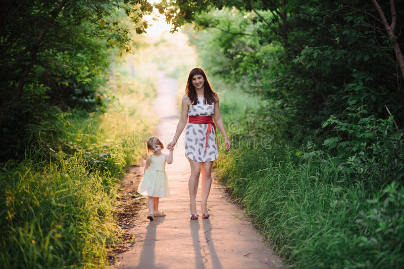 Mom keeps daughter's hand and walks the walk on the nature in sunset light. Motherhood, child, family royalty free stock photo