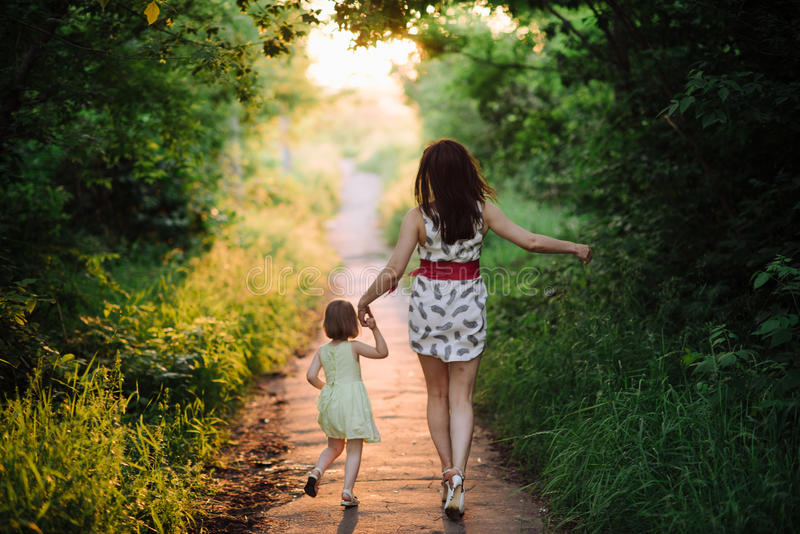 Mom keeps daughter's hand and walks the walk on the nature in sunset light. Motherhood, child, family royalty free stock image