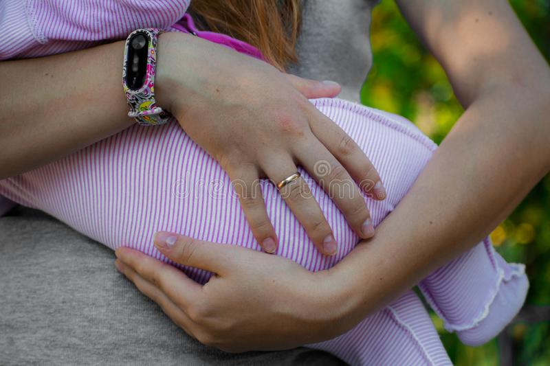 Mom keeps her newborn baby in her arms. Young mother keeps her small child. stock image