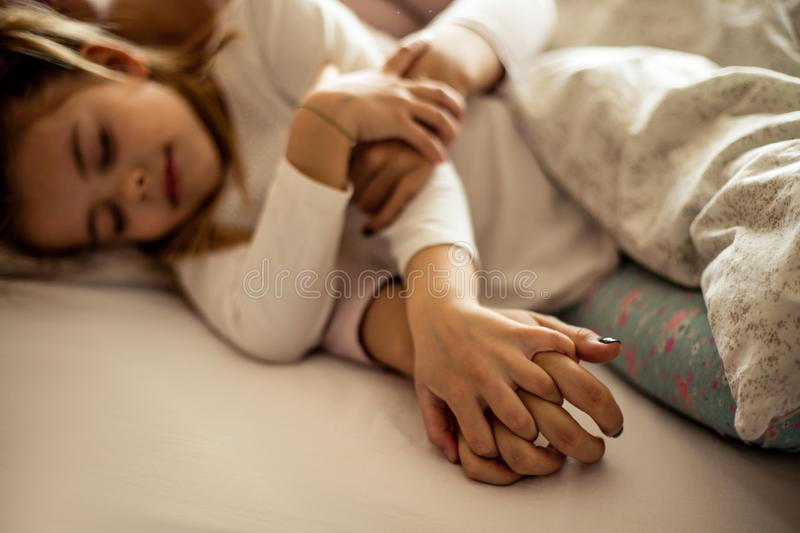 Mom keeps you. Mother and daughter sleeping together stock images