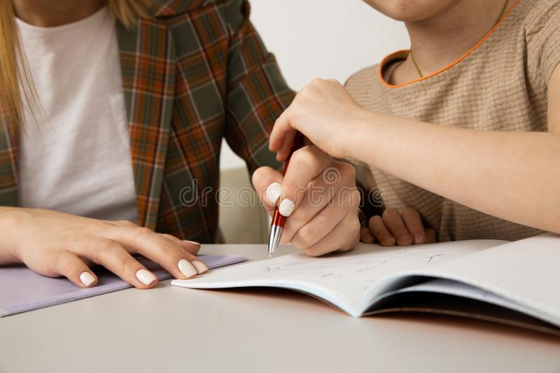 Mom and kid doing homework and writing task by pen. stock photos