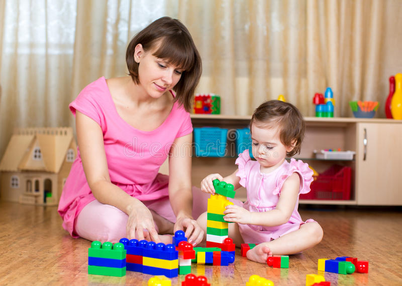 Mom and kid girl play block toys at home stock photos