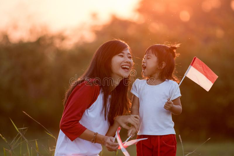 Mom and kid together with indonesian flag. Mom and kid having fun in the field with flag. indonesia independence day celebration concept royalty free stock images
