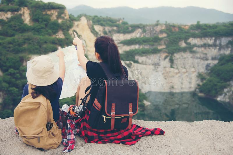 Mom and kid holding maps and travel backpacks sitting victorious facing on the grand canyon stock photography