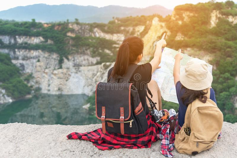 Mom and kid holding maps and travel backpacks sitting victorious facing on the grand canyon for education nature. Travel Concept royalty free stock images
