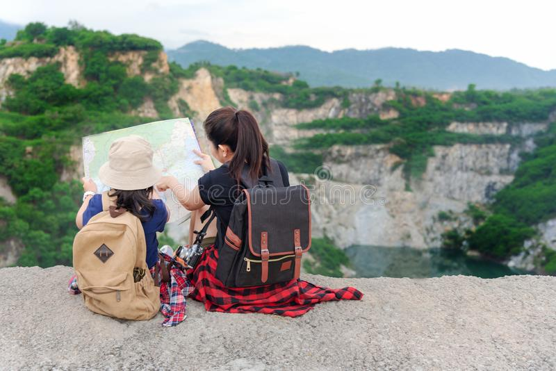 Mom and kid holding maps and travel backpacks sitting victorious facing on the outdoors grand canyon for education nature. royalty free stock photo