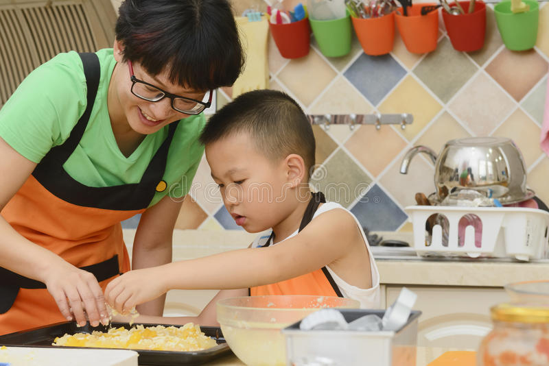 Mom and kid making pizza stock image