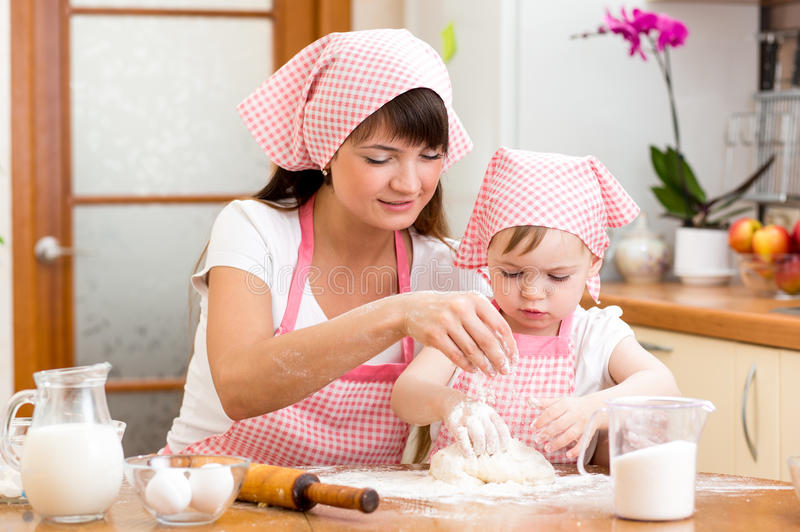 Mom and kid preparing cookies together at kitchen royalty free stock photos