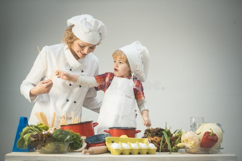 Mom and kid with smiling face cooking spaghetti together. Little chef concept. Mother teaches son to cook on light background. Chef and assistant near kitchen royalty free stock images