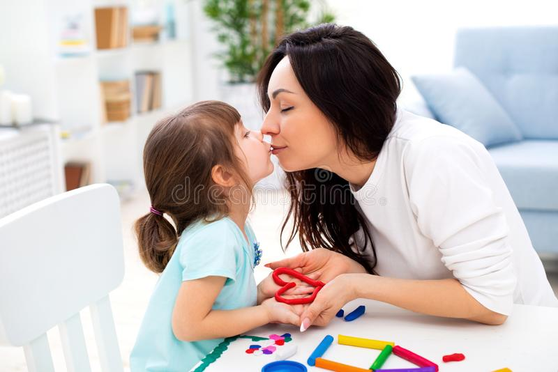 Mom kisses her little daughter. Happy family and family love. Mother and girl mold from plasticine, children`s creativity stock photography