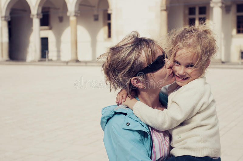 Mom kissing her daughter