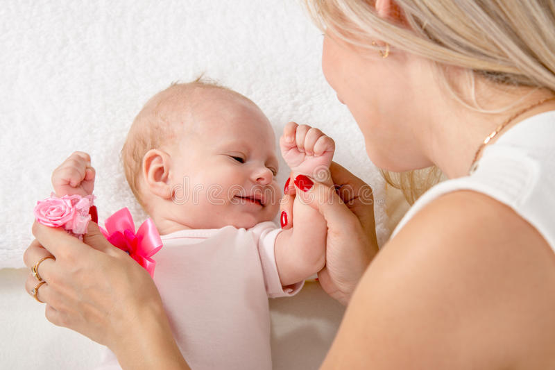 Mom kneads two-handle baby. A two-month baby lying on his back on the bed, sitting next to the child and mother looking at her royalty free stock photo