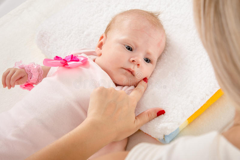 Mom leaned her finger to her cheek two-month girl. A two-month baby lying on his back on the bed, sitting next to the child and mother looking at her stock photos