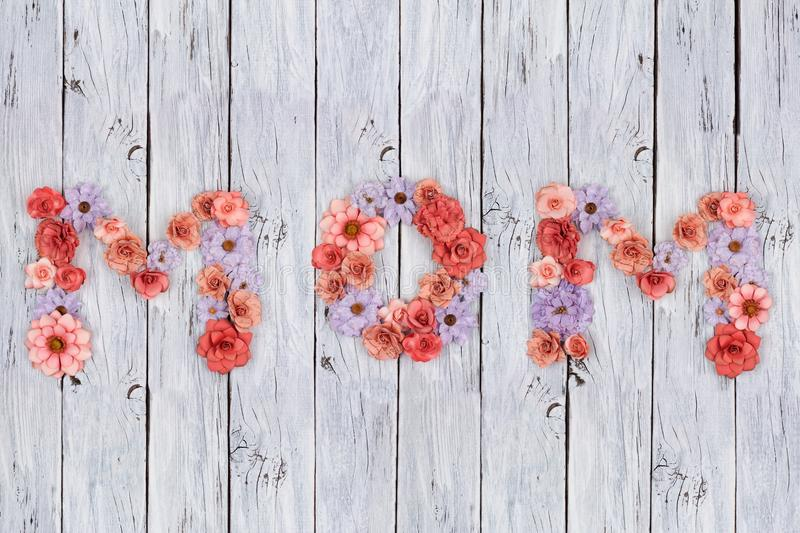 MOM letters made of paper flowers over aged white wood royalty free stock images