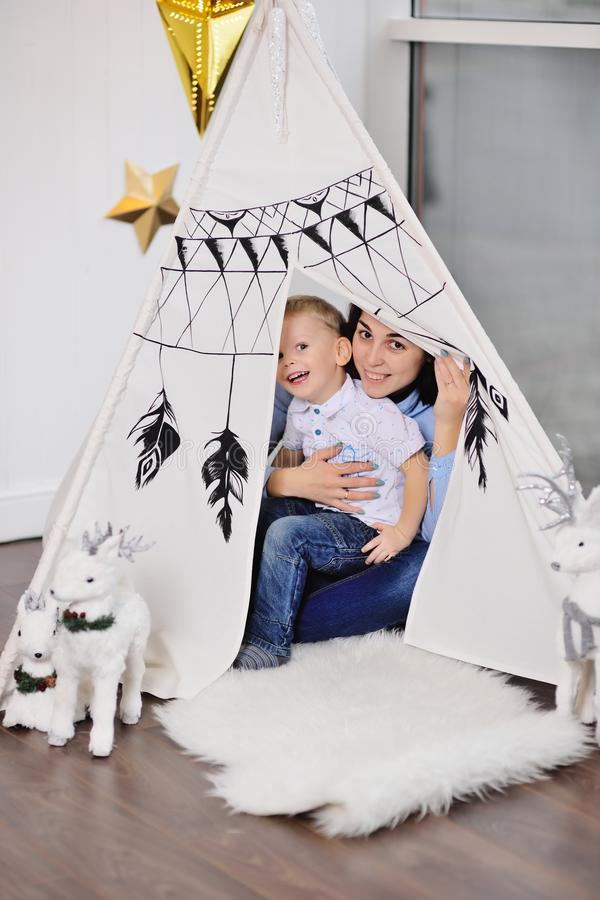 Mom and little baby boy hide in a tent or an Indian wigwam royalty free stock photo