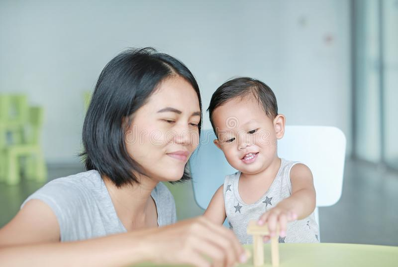 Mom and little baby boy playing wood blocks tower game for Brain and Physical development skill in a classroom. Focus at children royalty free stock images