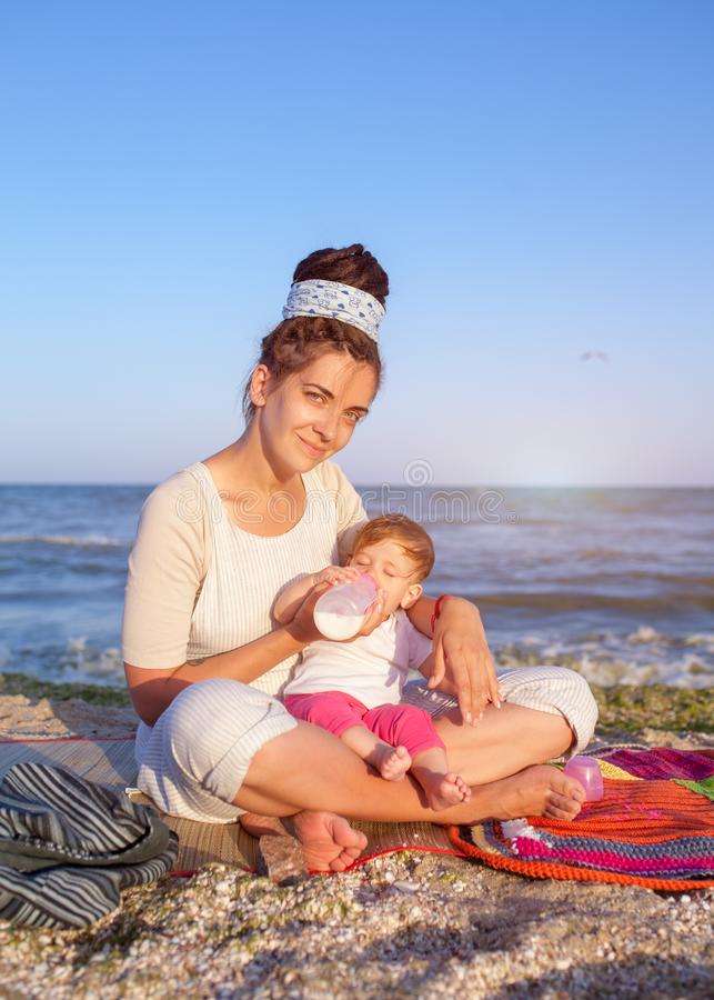 Mom and little child on the beach. Travel with a child. A woman feeds her daughter royalty free stock photo