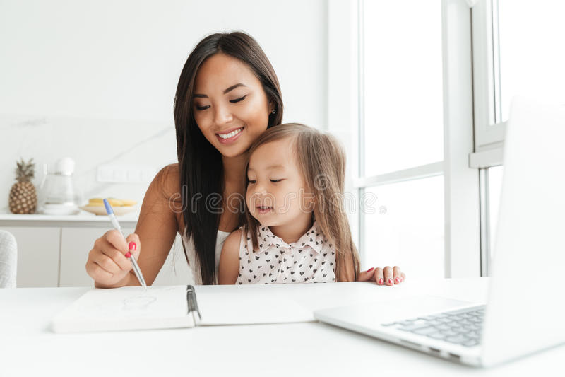 Mom with little cute asian girl using laptop writing notes royalty free stock photography