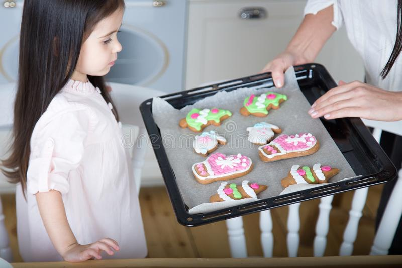 In the kitchen, mom and daughter bake cookies. Mom and little daughter bake Christmas cookies in the kitchen royalty free stock photo