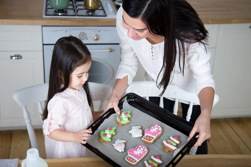 In the kitchen, mom and daughter bake cookies. Mom and little daughter bake Christmas cookies in the kitchen stock photos