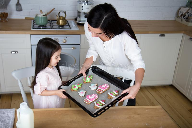 In the kitchen, mom and daughter bake cookies. Mom and little daughter bake Christmas cookies in the kitchen stock images
