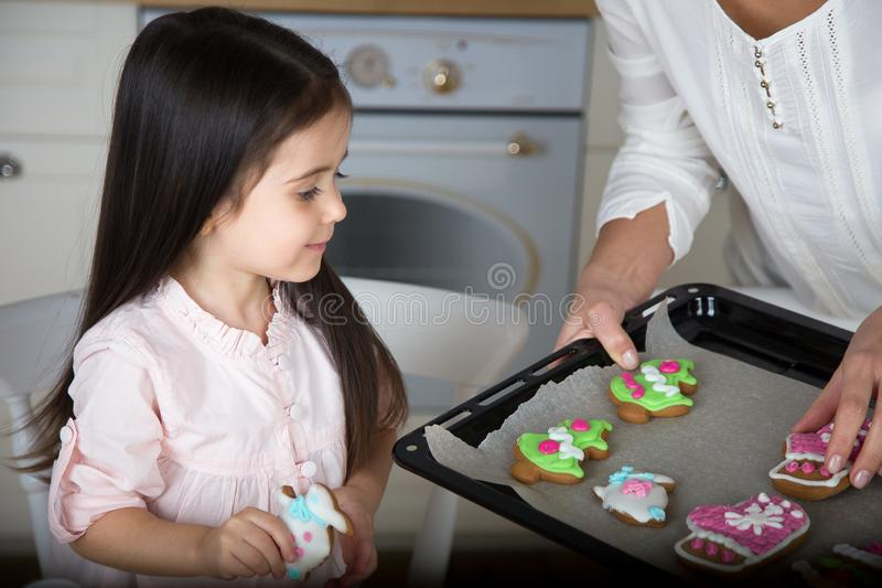 In the kitchen, mom and daughter bake cookies. Mom and little daughter bake Christmas cookies in the kitchen stock image
