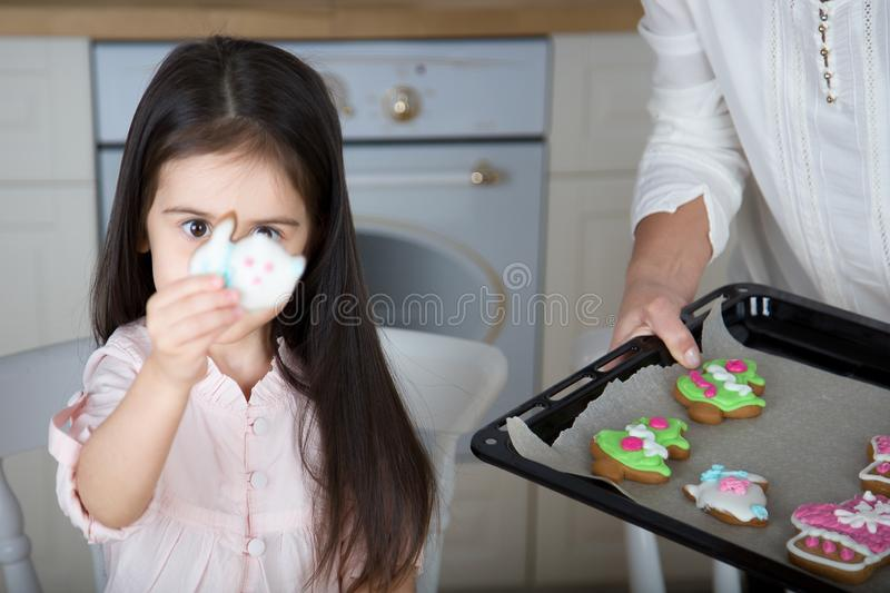 In the kitchen, mom and daughter bake cookies. Mom and little daughter bake Christmas cookies in the kitchen stock photography