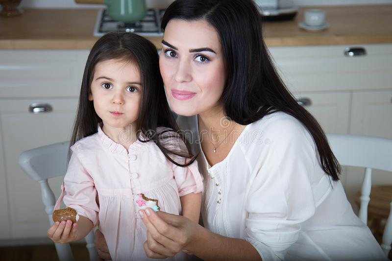 In the kitchen, mom and daughter bake cookies. Mom and little daughter bake Christmas cookies in the kitchen royalty free stock images