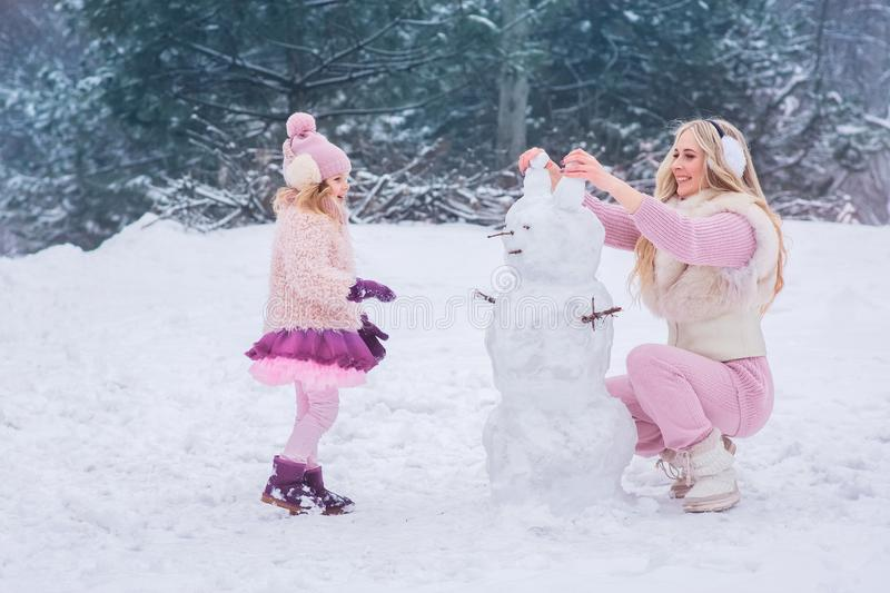 Mom and little daughter dressed in pink clothes have fun and make a snowman in a snowy park stock images