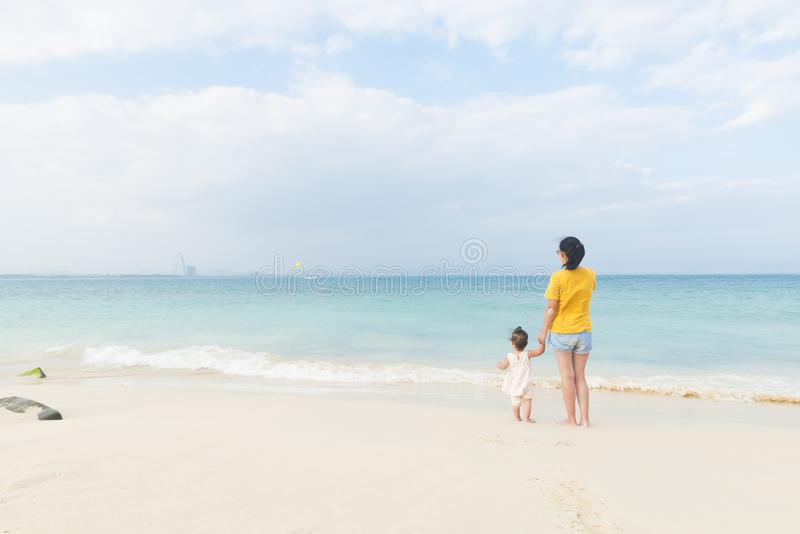 Mom and little daughter enjoy leisure time on beach royalty free stock images