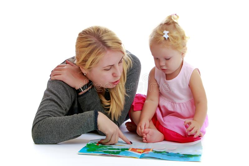 Mom and little daughter are looking at a book. royalty free stock photography