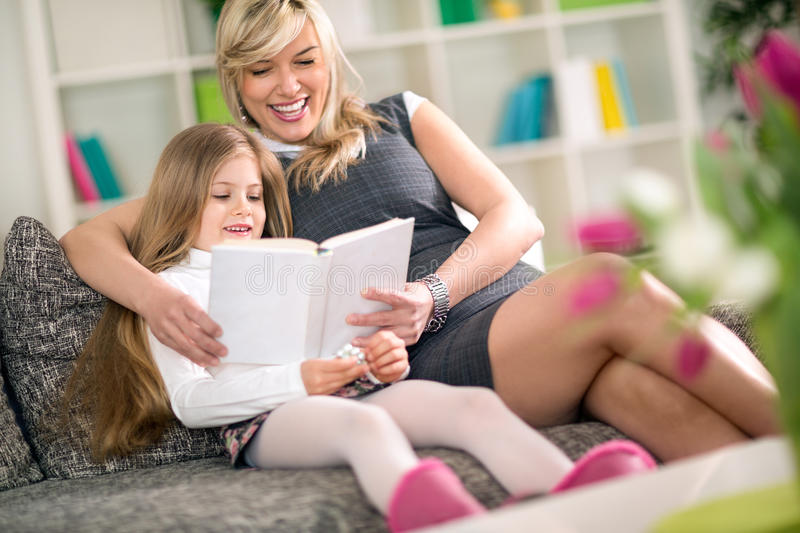 Mom with little girl reading book in sofa royalty free stock photos