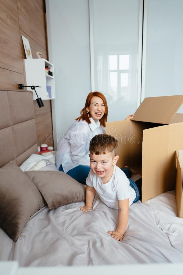 Mom and little son play in the bedroom with paper boxes. royalty free stock photography