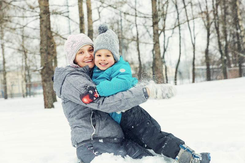 Mom and little son playing in the snow royalty free stock photo