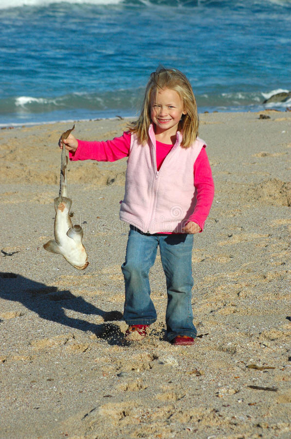 Child with shark. A beautiful Caucasian girl child with happy smiling facial expression holding a little dead shark in her hand and presenting it to her mom stock photography